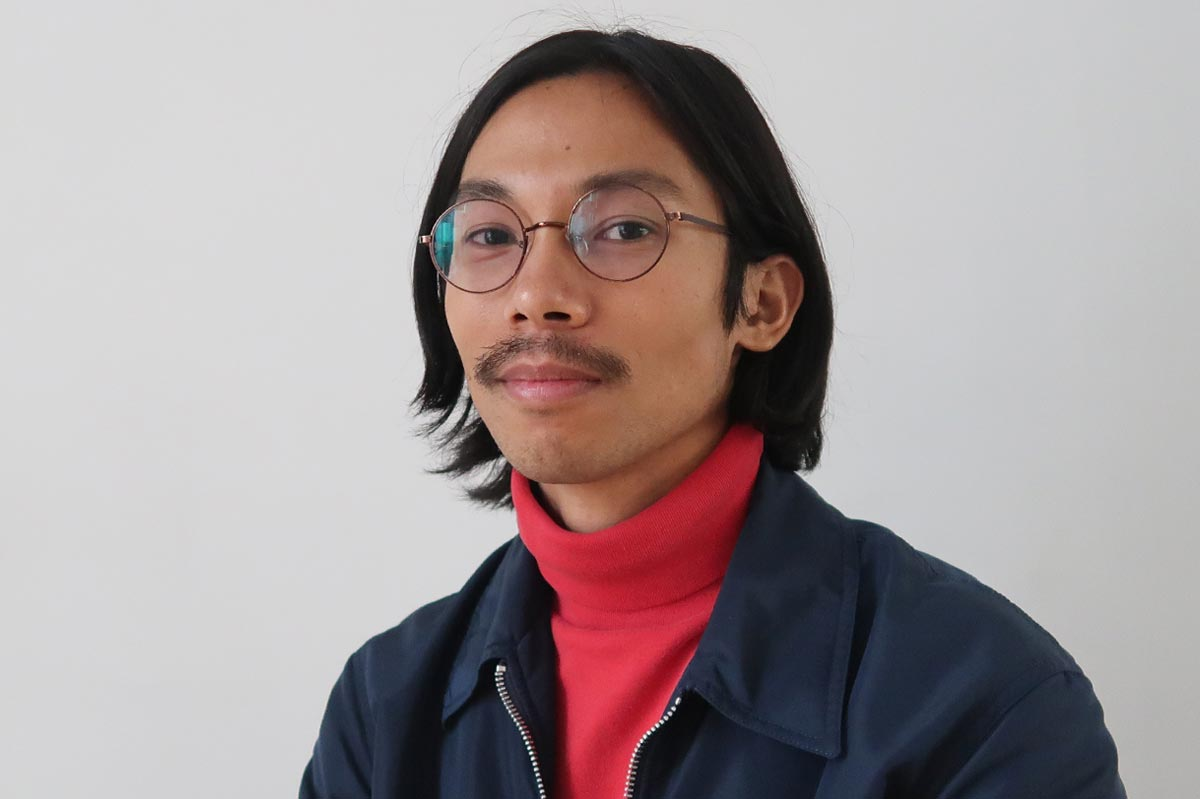 Miko Revereza, wearing a blue jacket and red turtleneck, sitting against a neutral gray background.