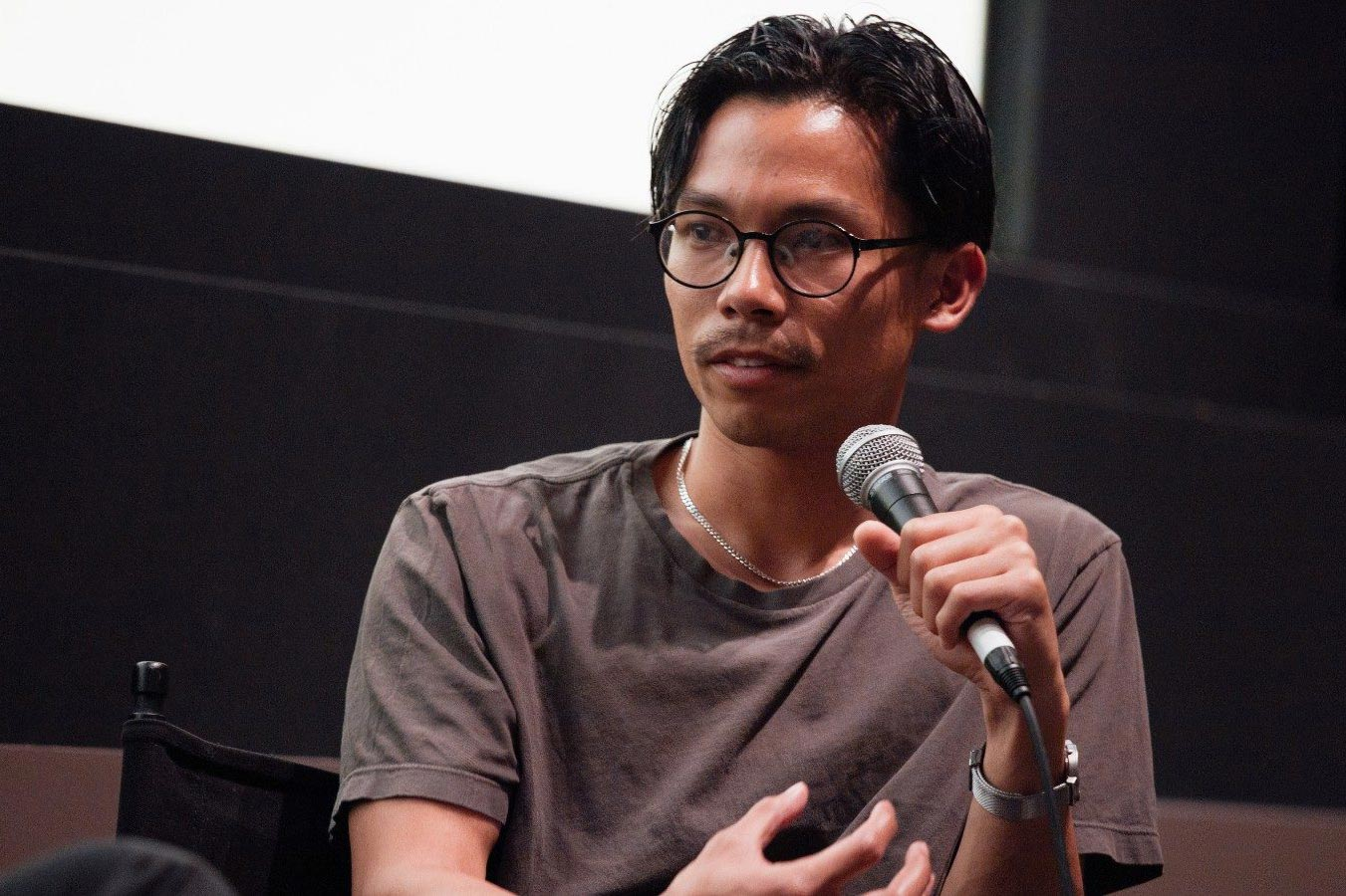 Miko Revereza holding a microphone and speaking at a Q&A in front of a movie theater screen.