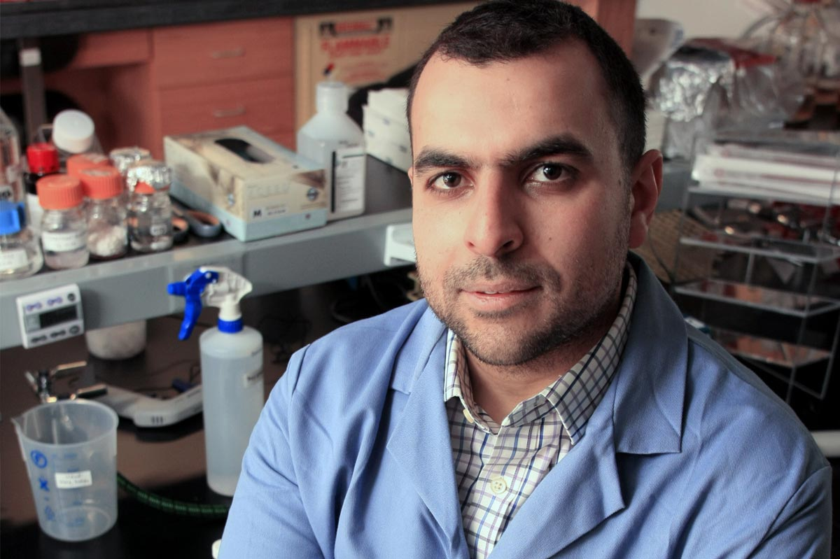 Mohamed Abou Donia, donning a lab coat, in his science lab.