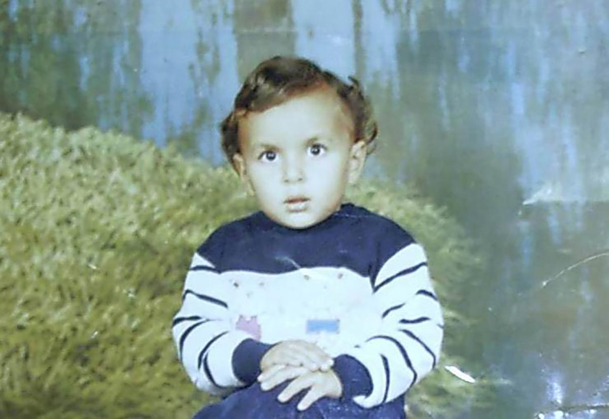 Mohamed Abou Donia at age 3, wearing a blue and white sweater.