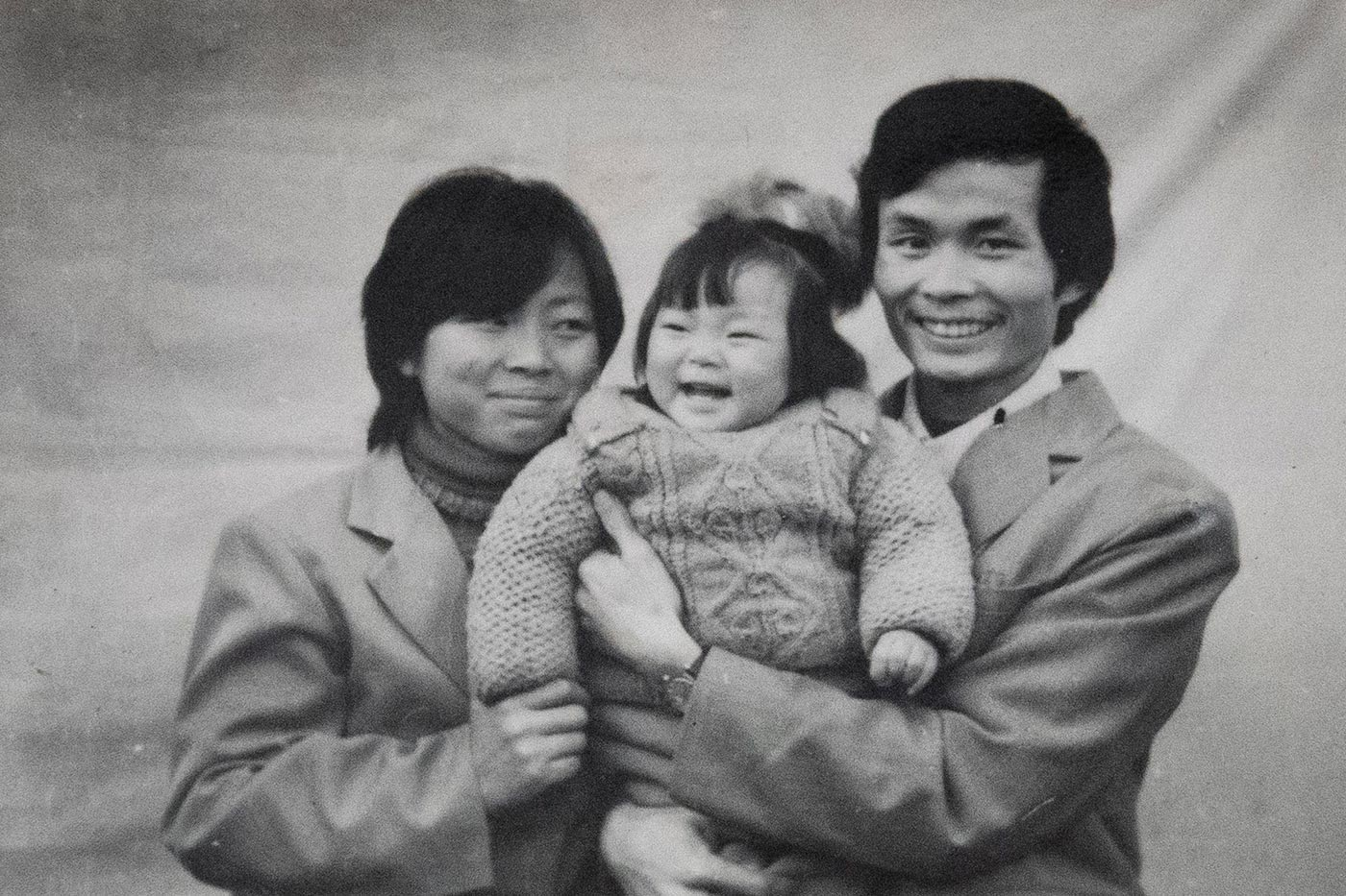 Nanfu Wang, at age 1, being held by her mother and father.