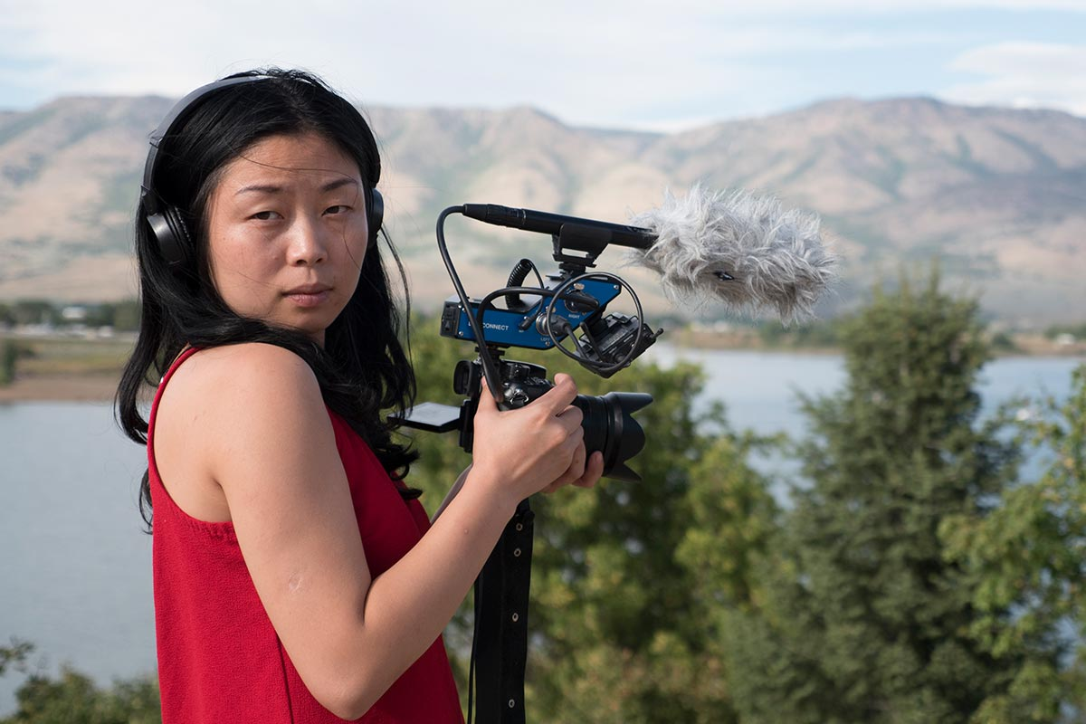 Nanfu Wang, holding a camera and microphone, filming on location in Florida with trees, mountains, and water in the distance.