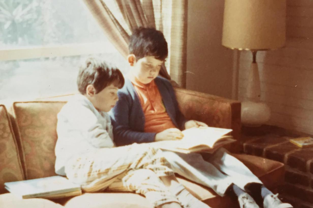 Rodrigo Prieto, as a child, sitting on a couch with his brother reading a book.