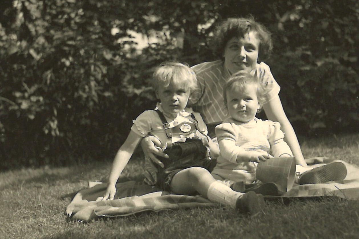 Ruth Lehmann, sitting with her mother and brother on a blanket in the grass.