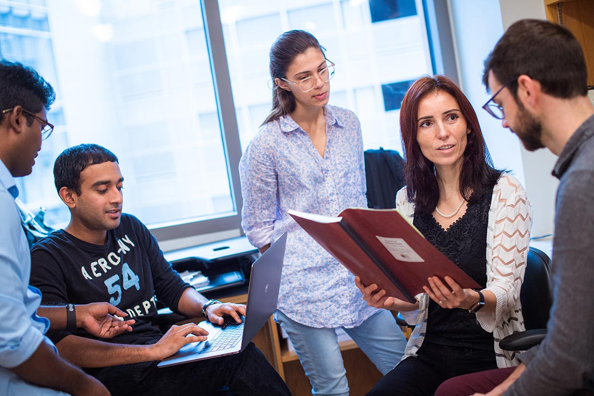 Silvi Rouskin holding a report and talking with graduate students.