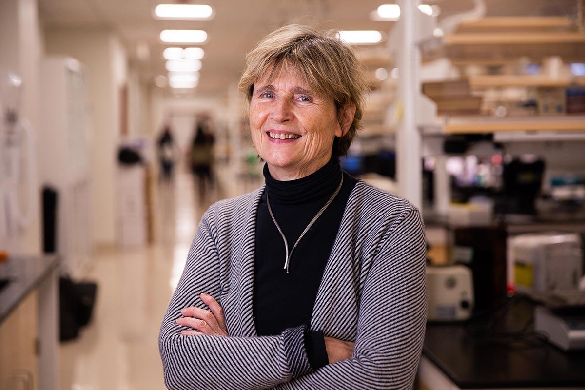Ruth Lehmann smiling, arms crossed, standing in her science lab.