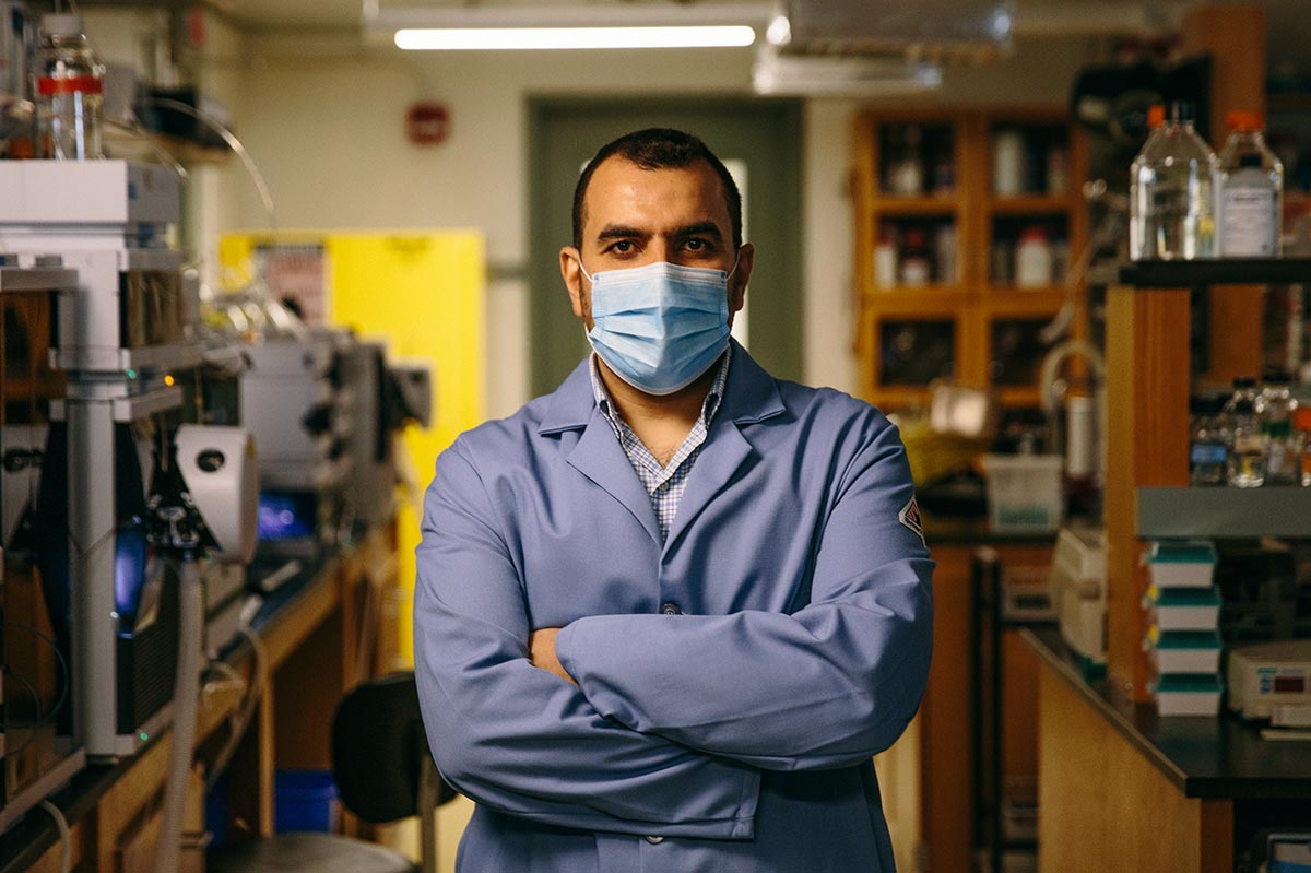 Mohamed, arms crossed and wearing a lab coat, stands in his Princeton University lab.