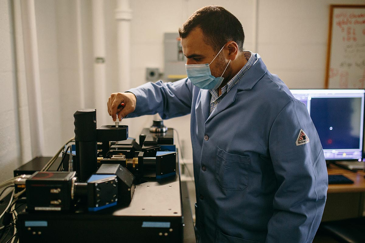 Mohamed, wearing a lab coat and mask, adjusts lab equipment.