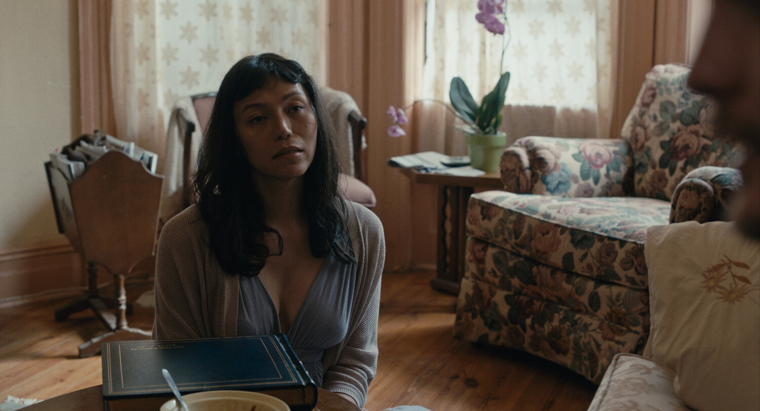A film still of Olivia, a Filipina trans woman, looking off-screen while sitting by a coffee table.