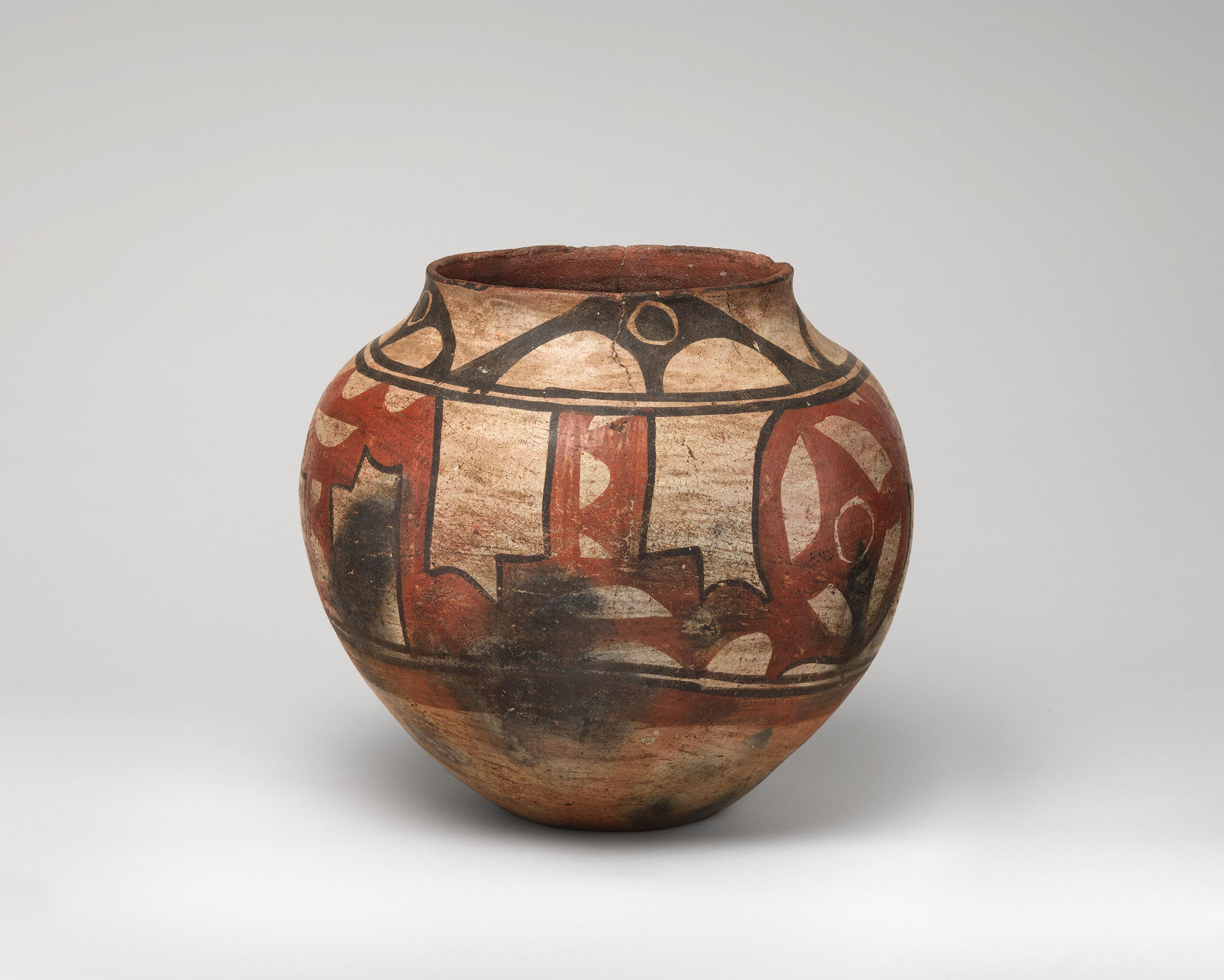 Santa Ana polychrome water jar featuring white slip with black and red painted decoration.