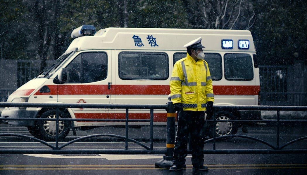 A still frame of an officer stands in front of an ambulance, from the film 76 Days.