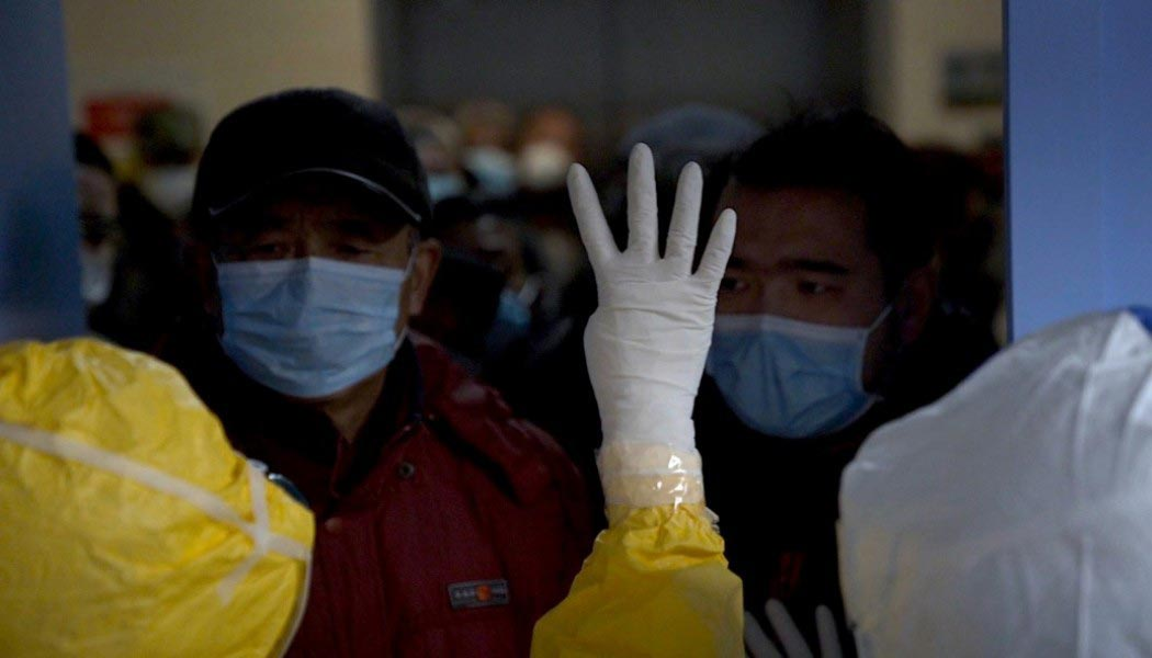 A crowd of people are separated by a door and medical personnel wearing PPE.