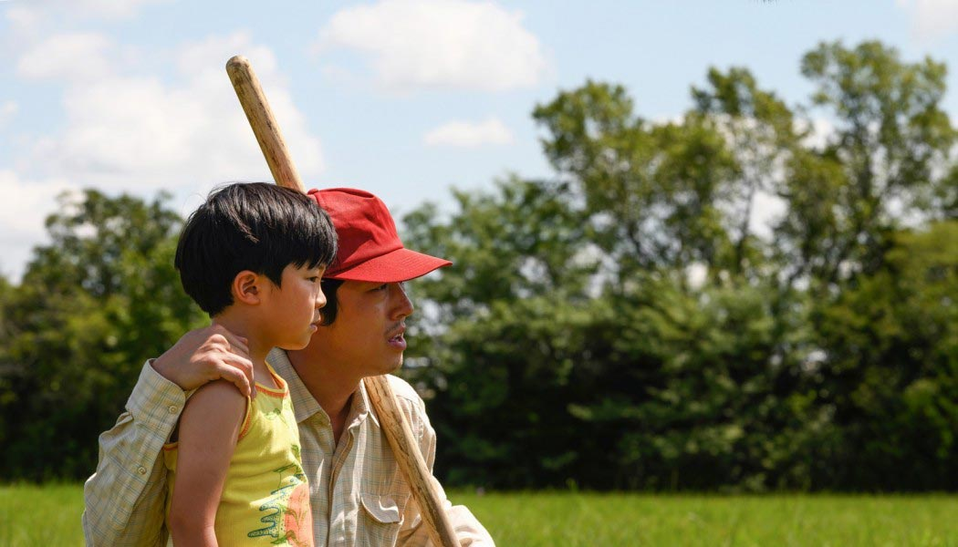 A film still of Steven Yeun, wearing a red hat, with arm around his on-screen son.