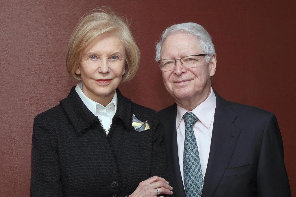 Marica and Jan Vilcek in front of a red wall.
