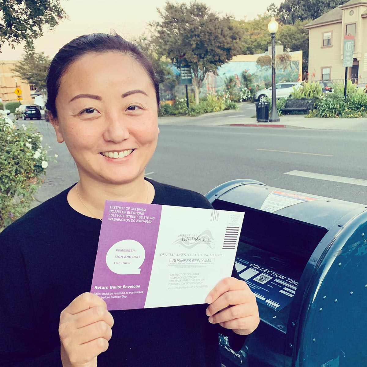 Yi Chen holding up a mail-in ballot in front of a USPS mailbox.