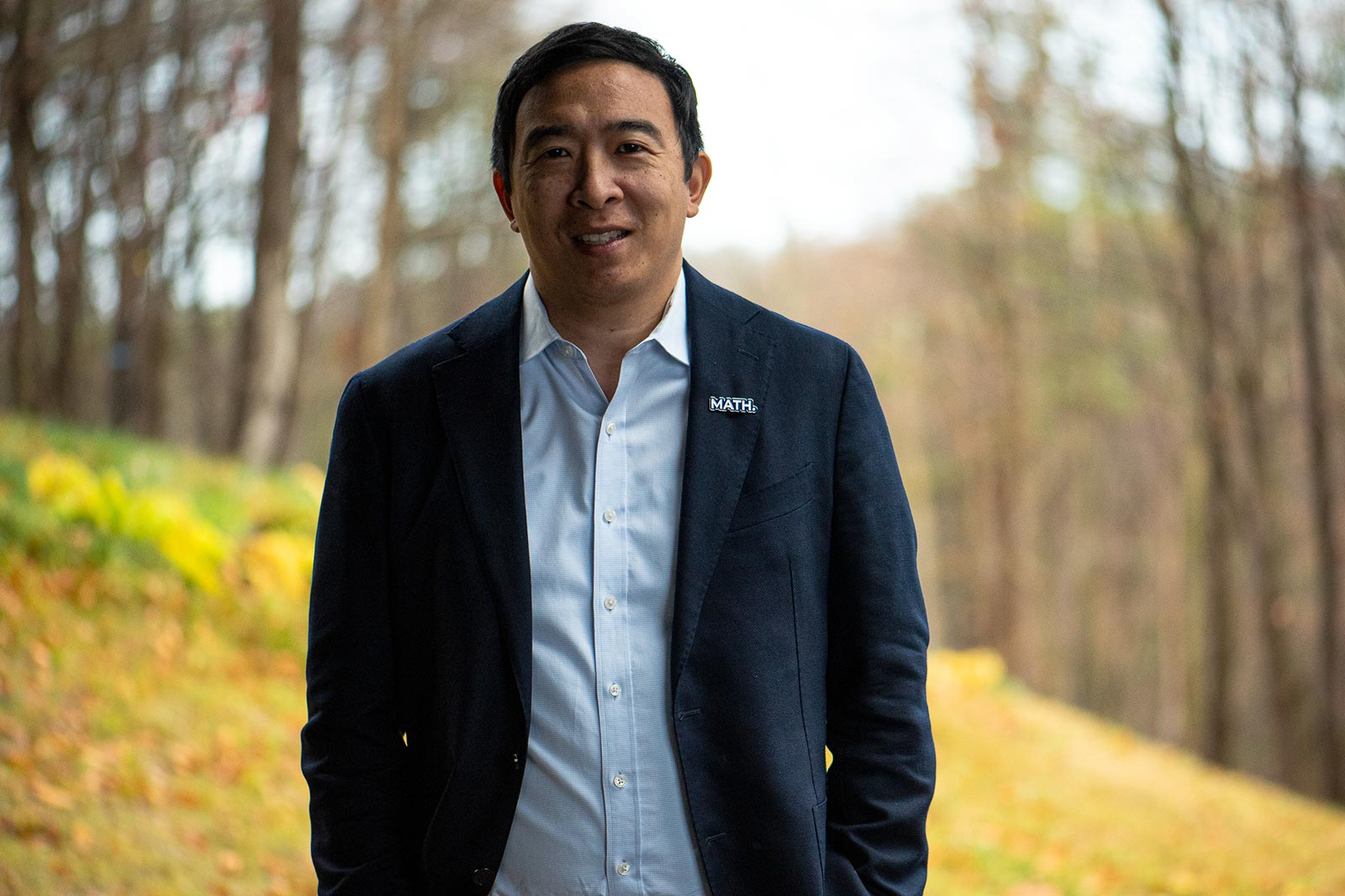 Portrait of Andrew Yang in upstate New York with trees and a hill behind him.