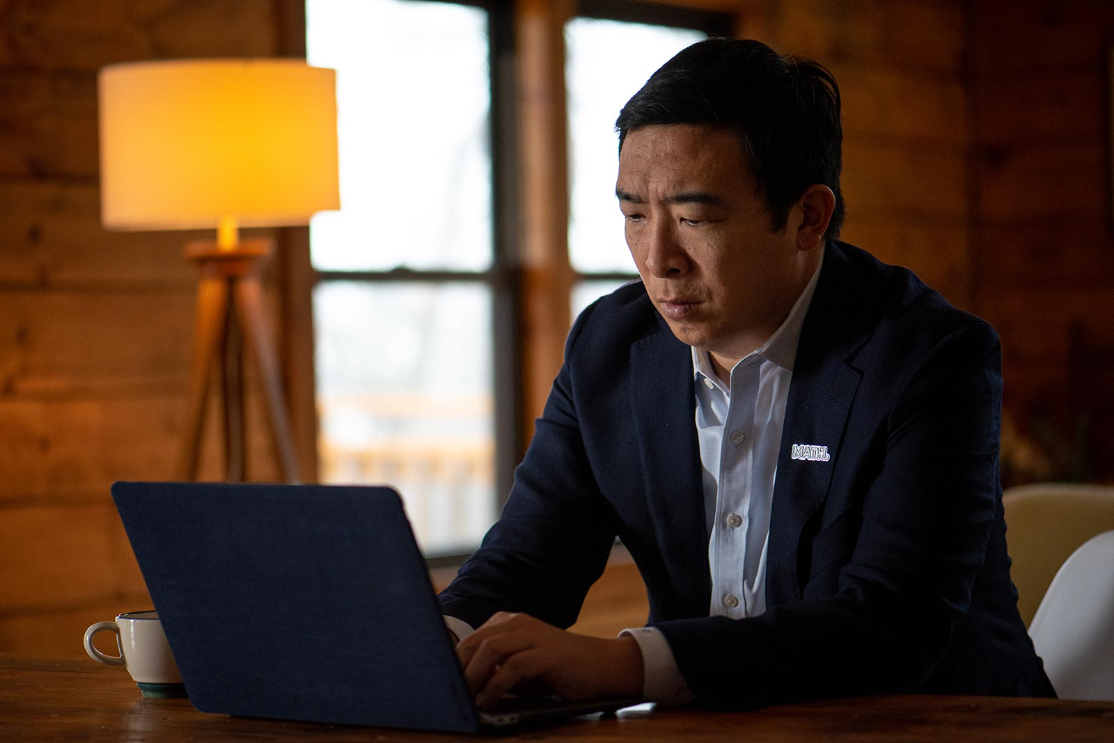 Andrew Yang, in blue suit jacket and MATH pin, sitting at a table typing on a laptop.
