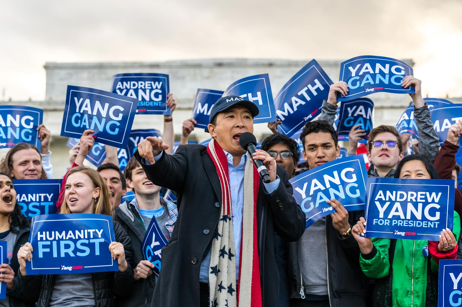 Andrew Yang, holding a microphone at a presidential campaign rally, surrounded by supporters holding Andrew Yang for President signs.