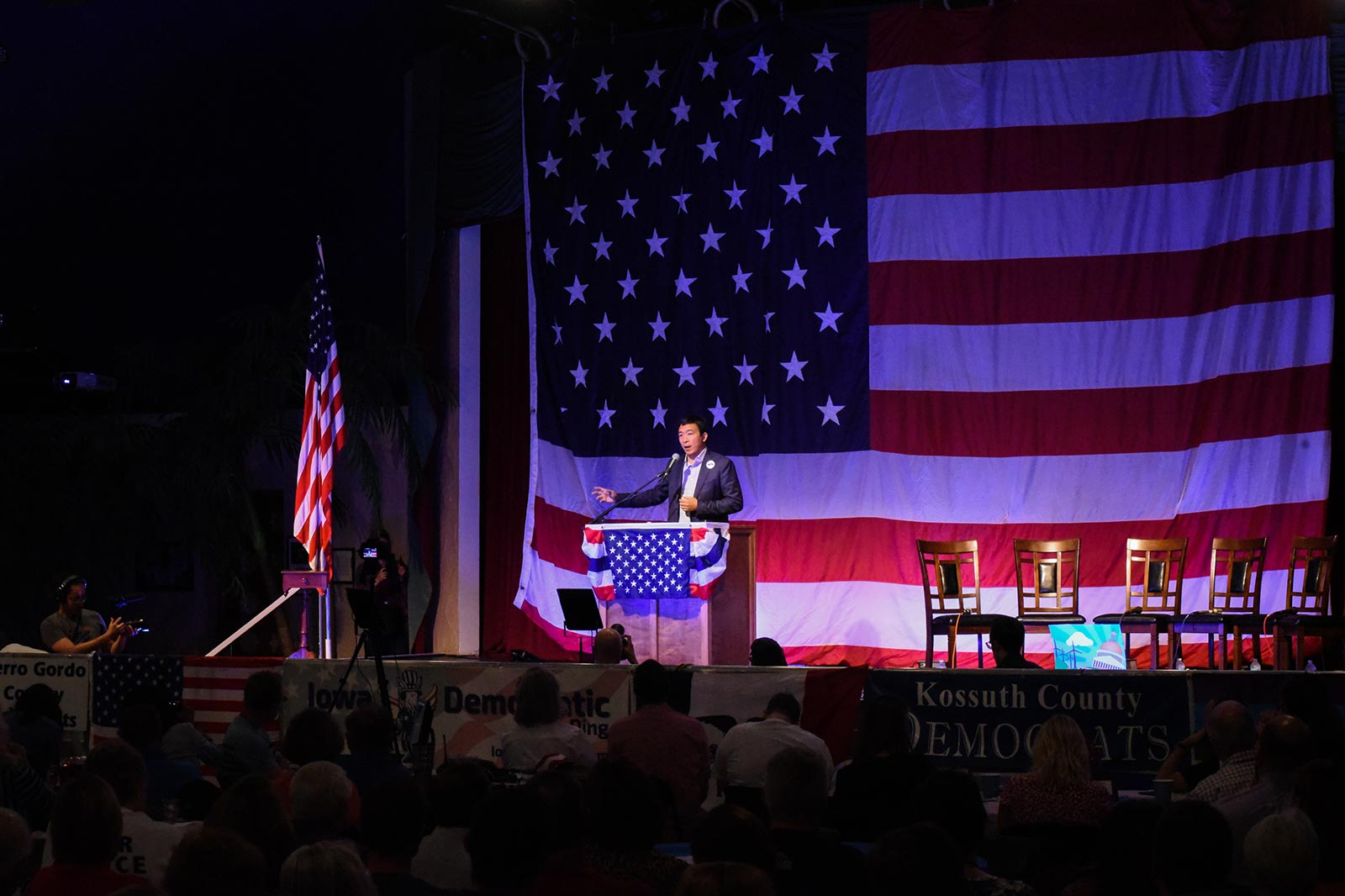 Andrew Yang at a podium on a stage against a backdrop of an American flag.