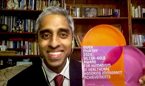 Vivek Murthy holds up the VIlcek-Gold heart-shaped award during an online presentation.