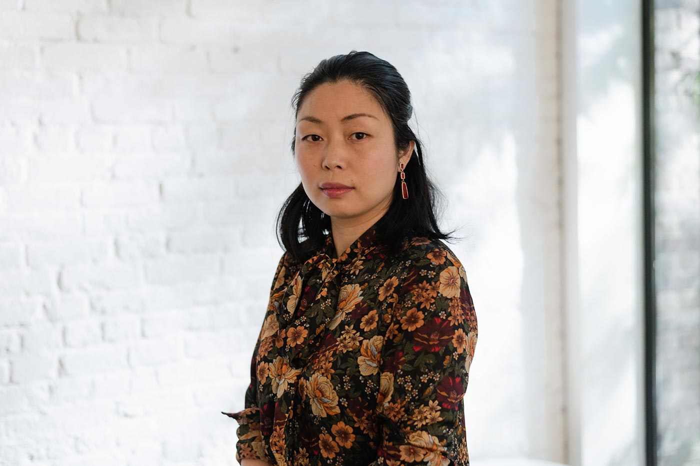 Nanfu Wang, in a floral shirt, standing in front of a white brick wall.