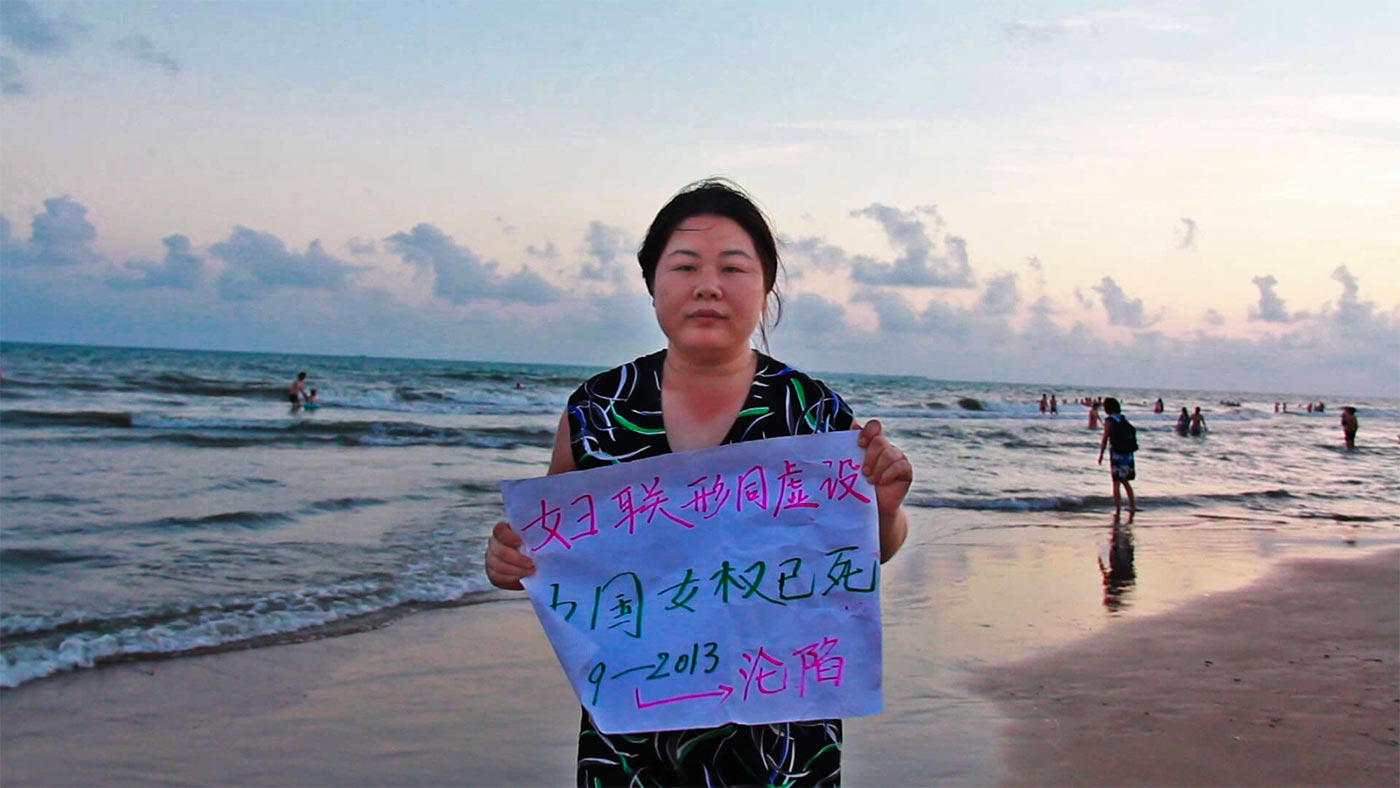 A still frame of Chinese activist Ye Haiyan holding a sign on a beach, from the film Hooligan Sparrow.