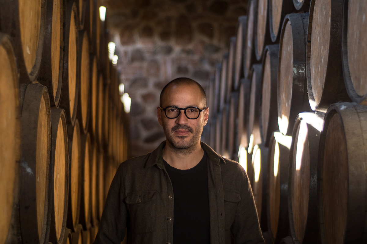 Juan Pablo González standing in a cellar surrounded by barrels.