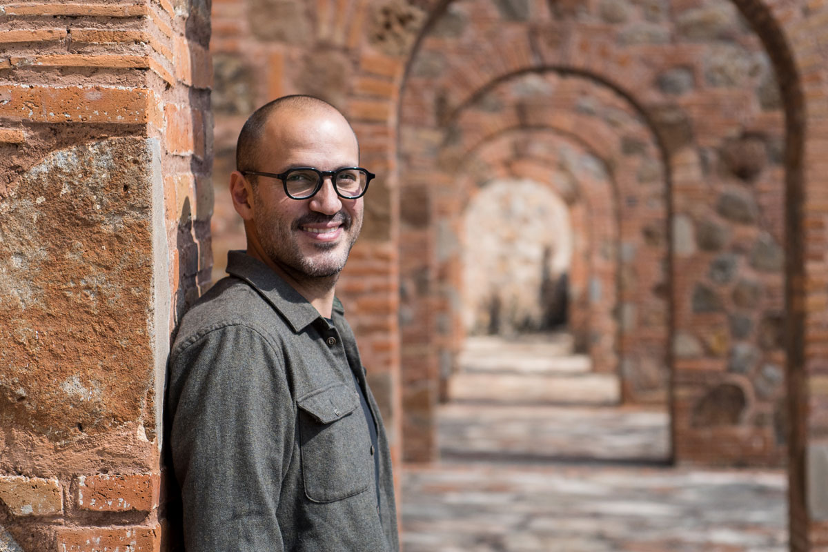 Juan Pablo stands to the left of multiple brick archways.