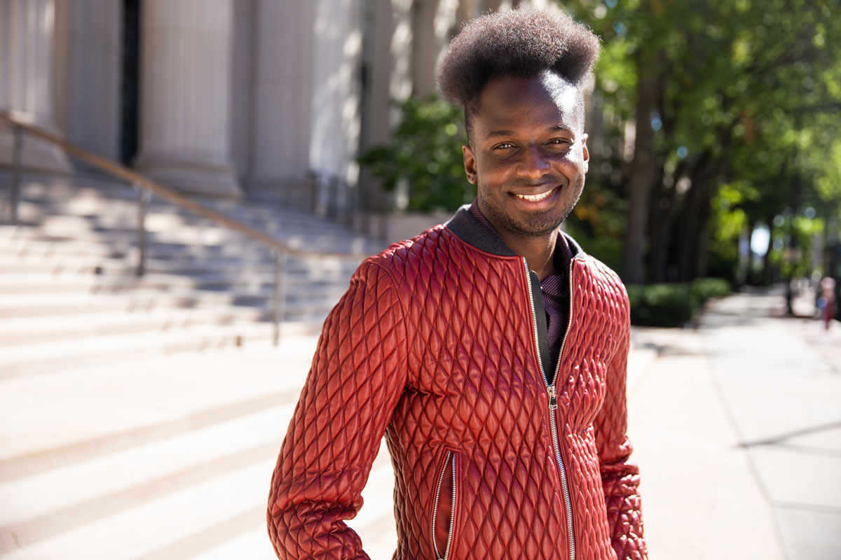Ibrahim Cissé with a big smile, wearing a red jacket, standing in front of the steps of an MIT building.