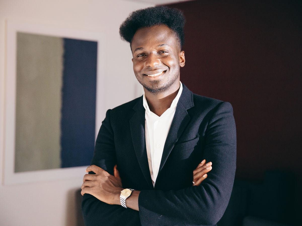 Ibrahim Cissé with a big smile, arms folded, and a black blazer.
