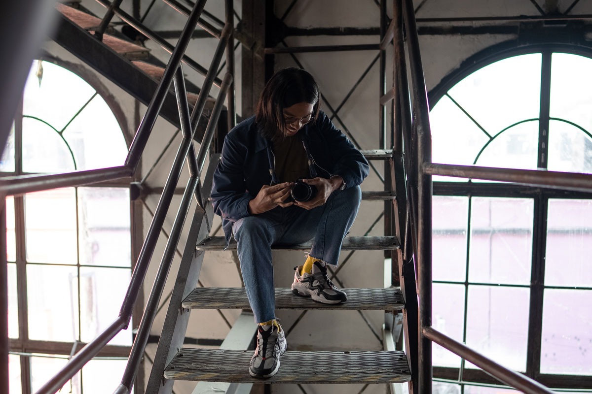 Miko Revereza sitting on the metal stairs of a warehouse inspecting his camera.
