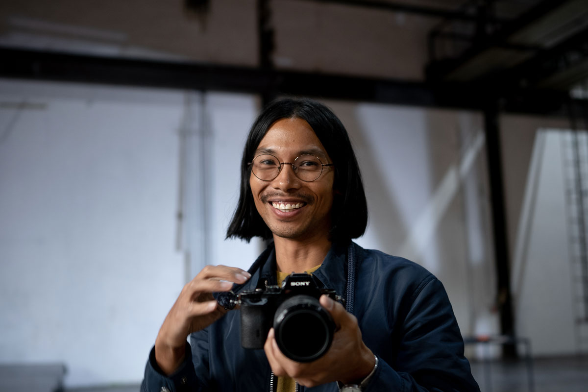 Miko Revereza points his lens towards the camera with a smile on his face.