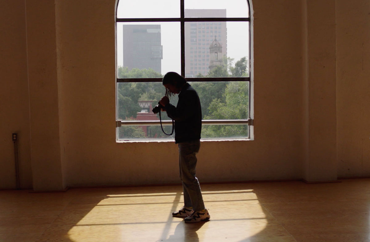 Miko Revereza stands in front of a bright window looking into his camera.