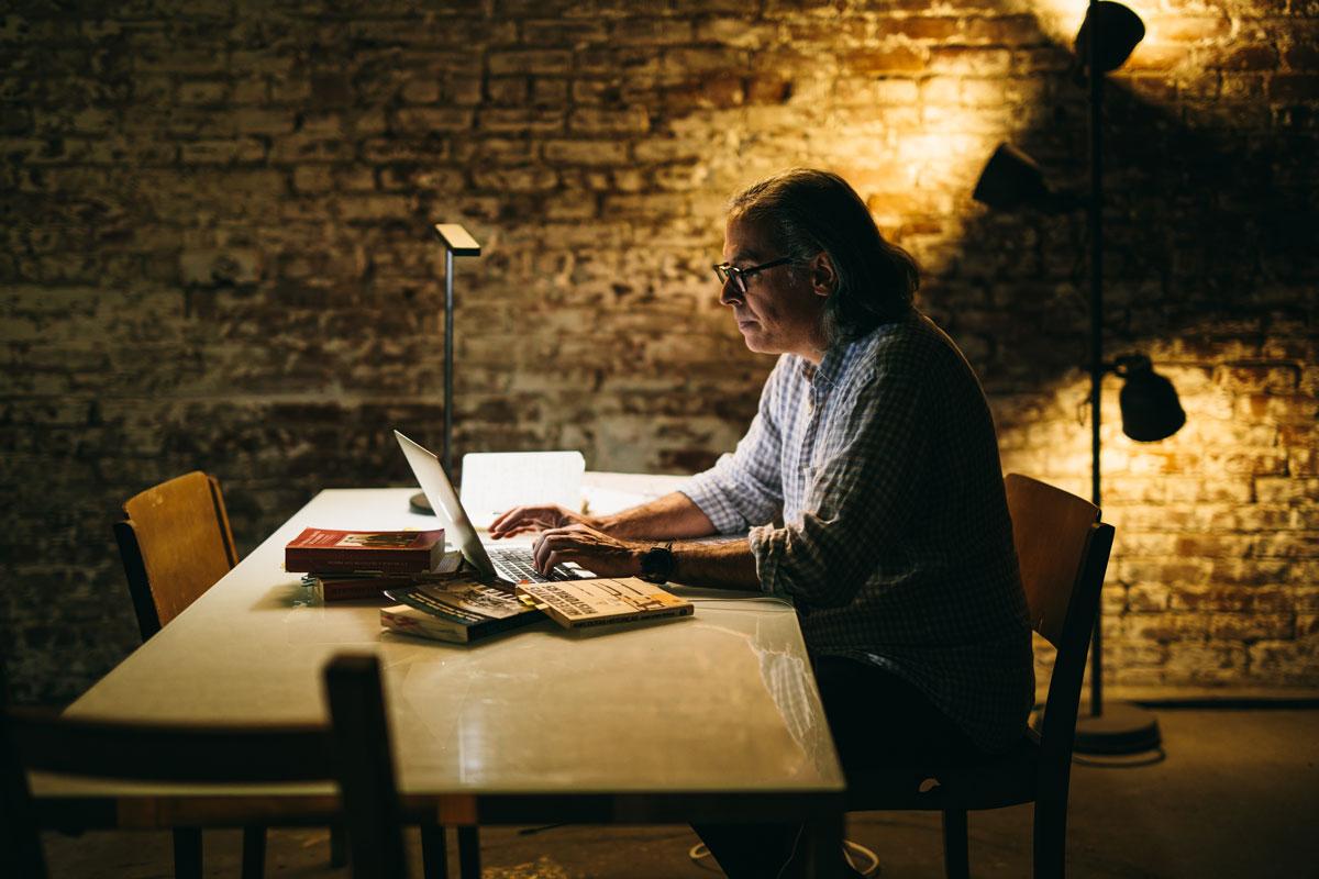 A side profile of Rodrigo Prieto working in lowlight on his laptop.