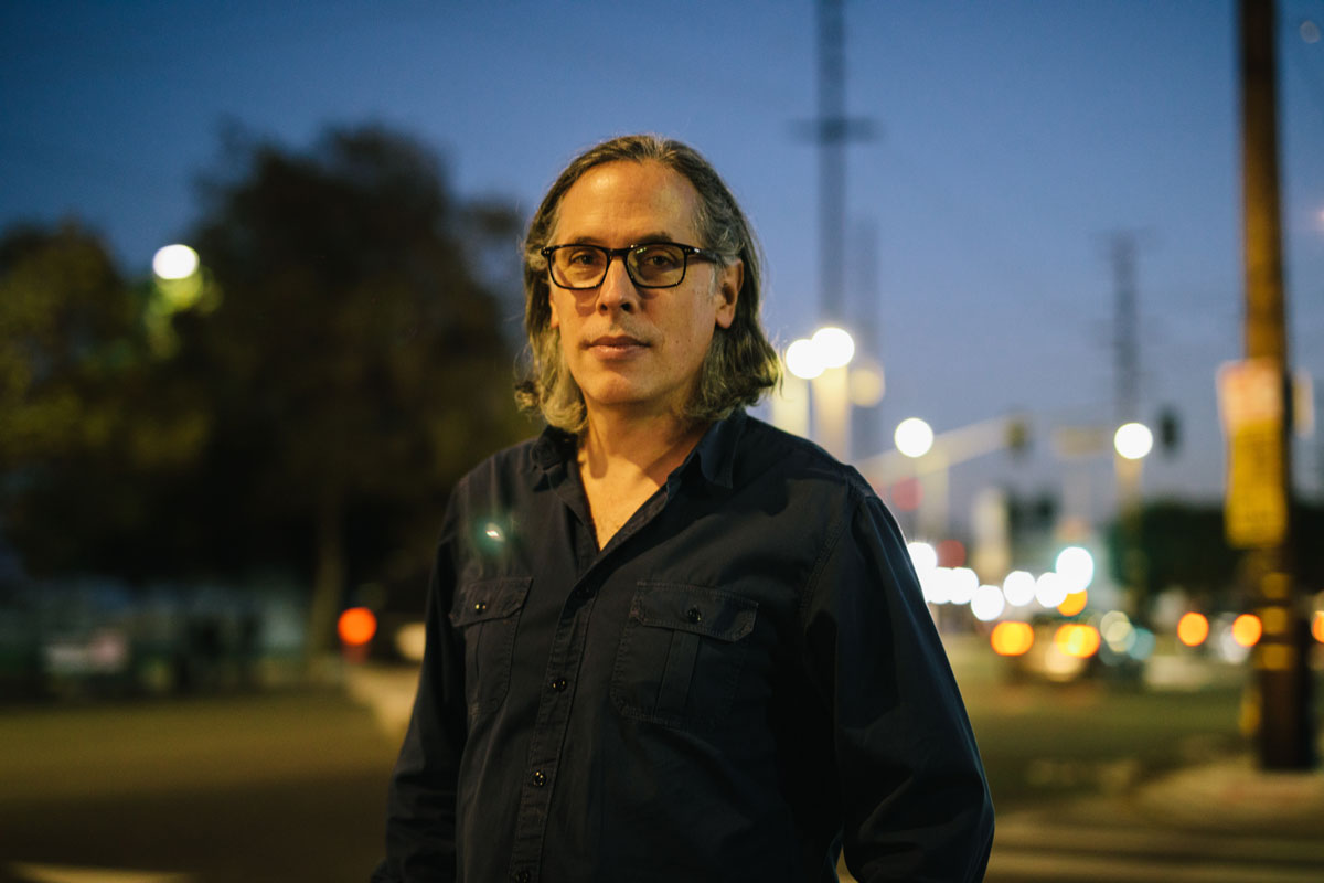 Rodrigo Prieto in a blue button-down with the evening lights of Los Angeles behind him.