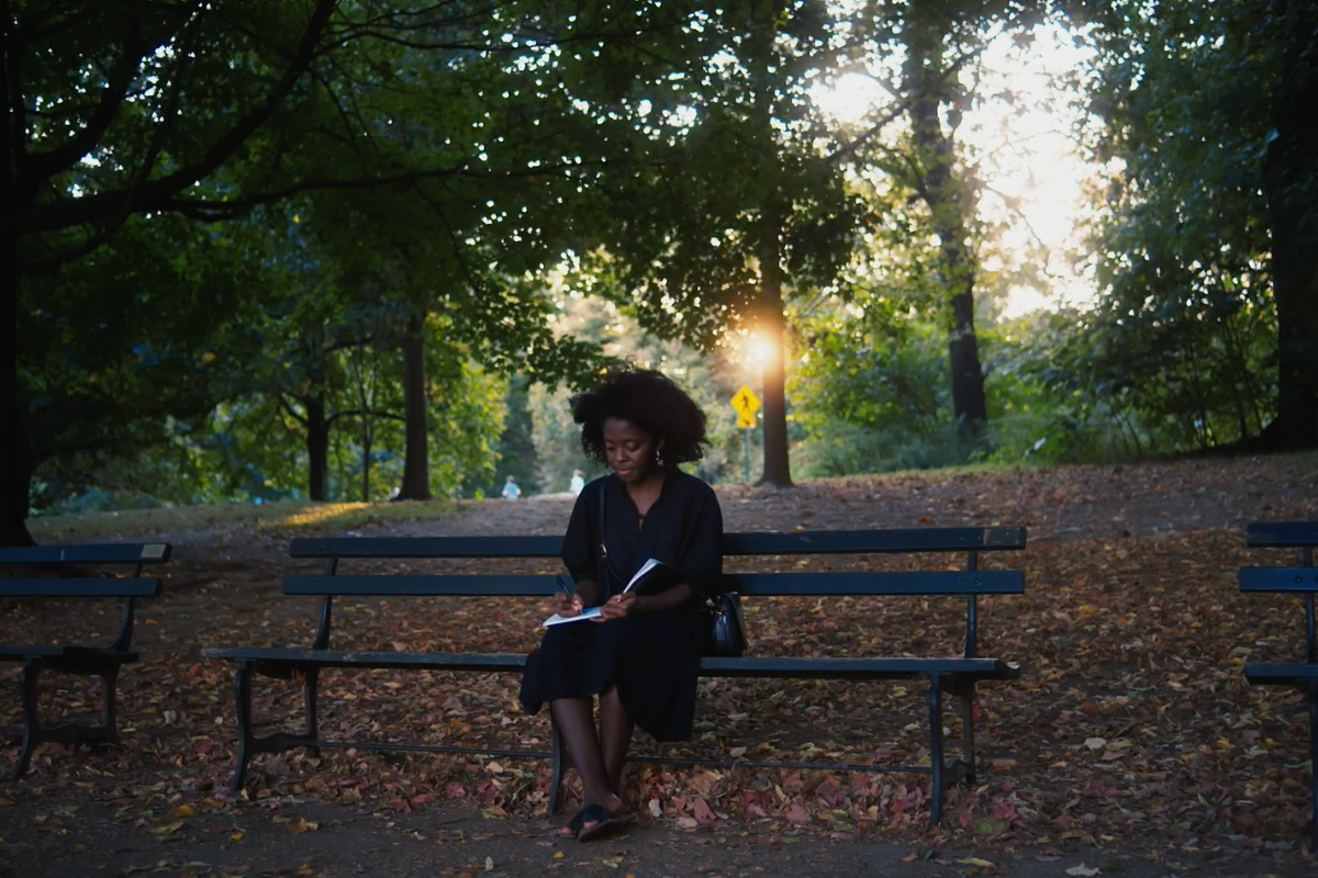 Yaa Gyasi sits on a park bench reading surrounded by green trees.