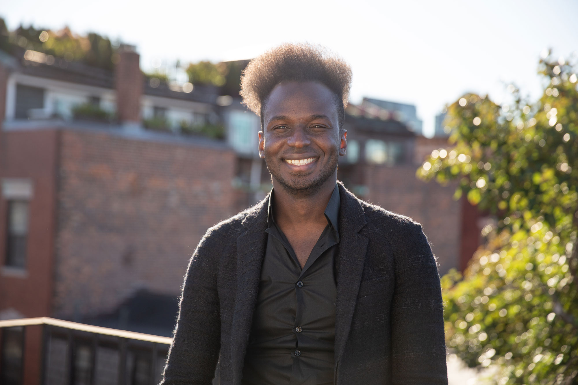 Ibrahim Cissé wearing a black blazer and shirt, smiles standing on a rooftop.