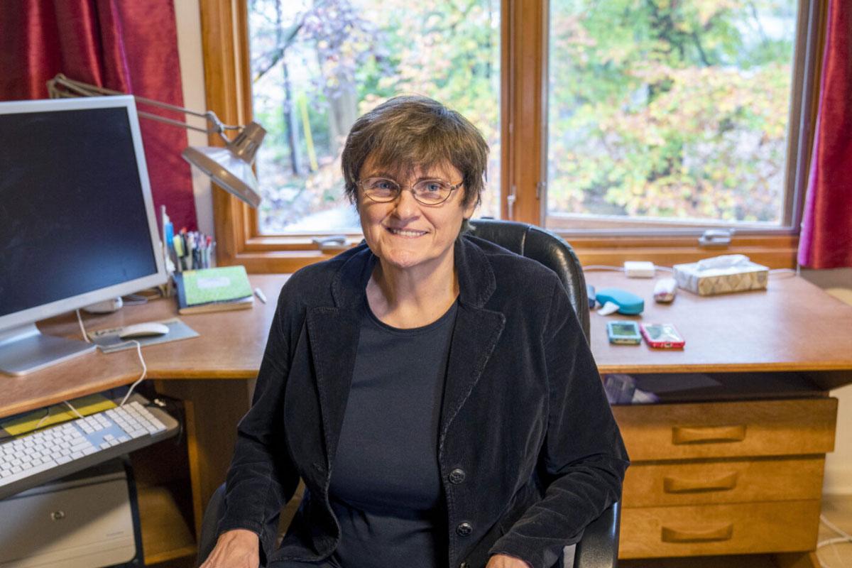 Katalin Karikó sits in her home office dressed in a black blazer.