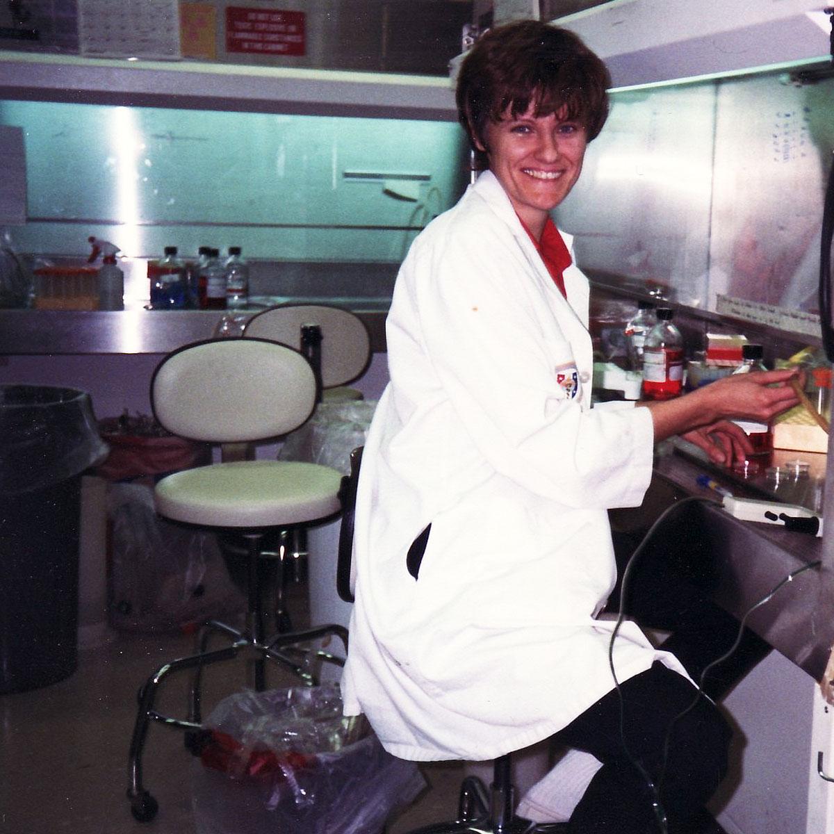A young Dr. Katalin Karikó smiling in a lab coat.