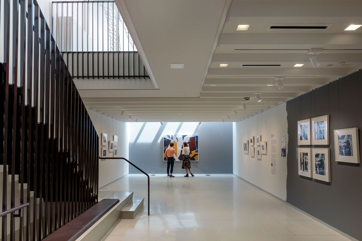 The first floor gallery space of The Vilcek Foundation with a brass staircase and skylight.