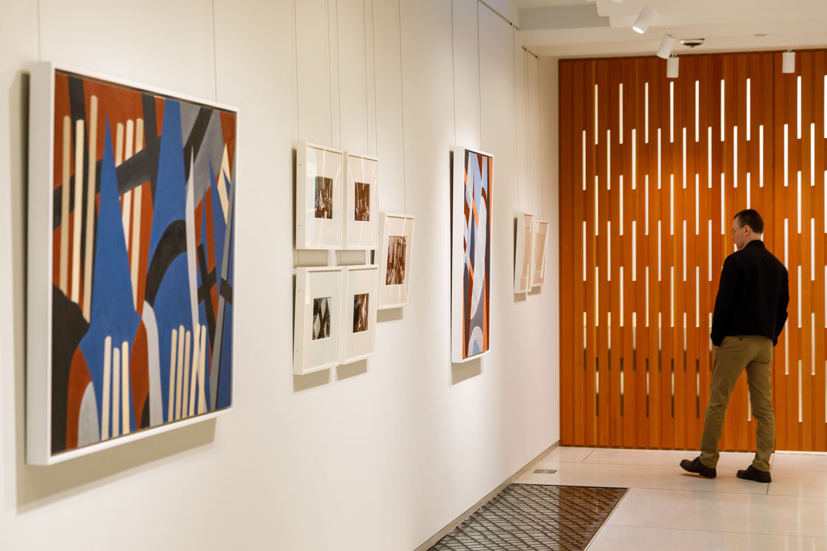 The second floor gallery space with multiple works on the walls, and the decorative wooden exterior of the boardroom.