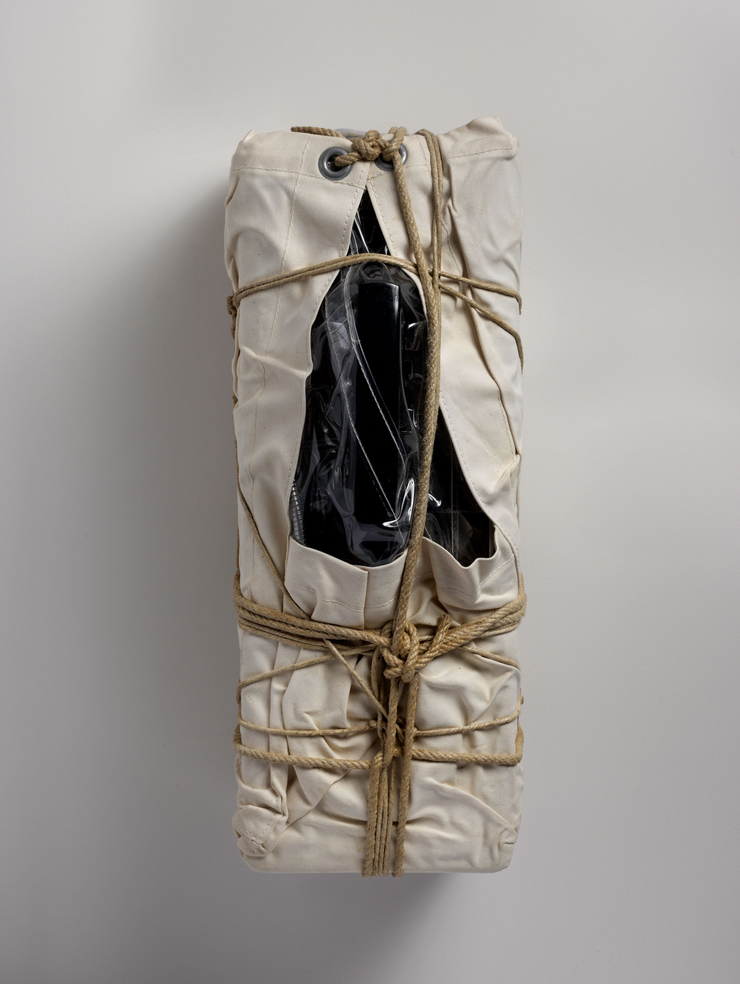 Photograph of a payphone wrapped in sackcloth with rope and twine.