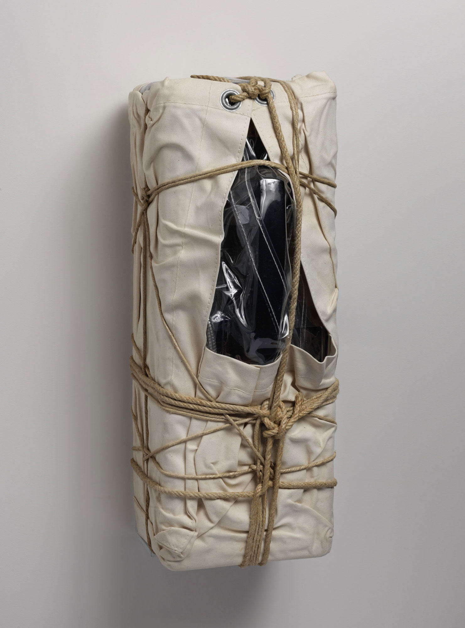 Side view of a payphone wrapped in sackcloth with rope and twine.