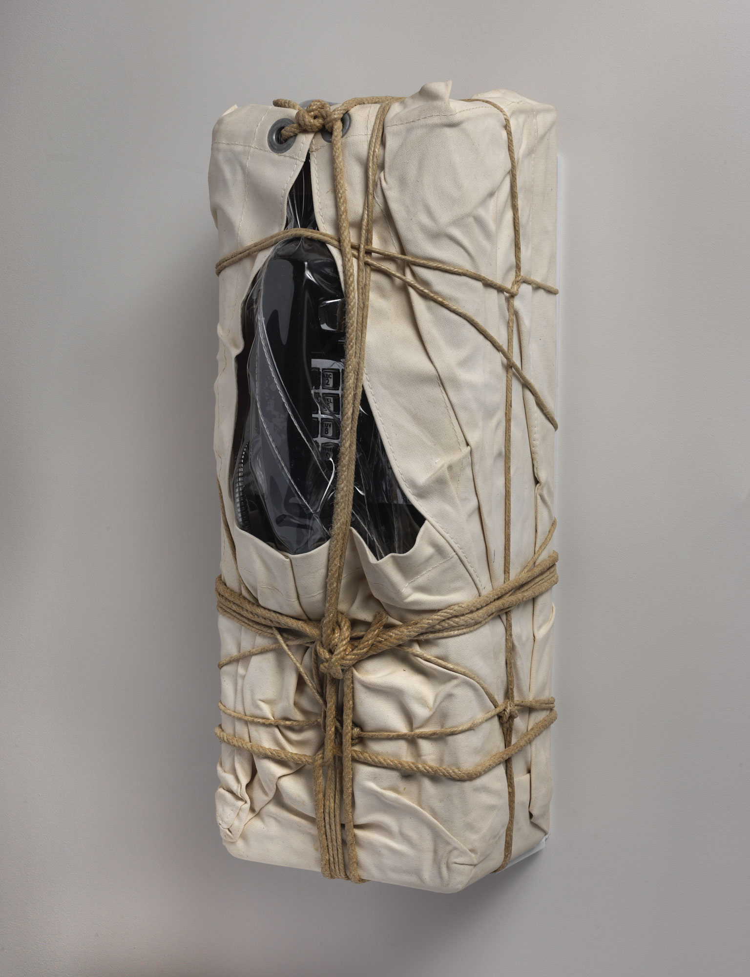 An alternate side view of a payphone wrapped in sackcloth with rope and twine.
