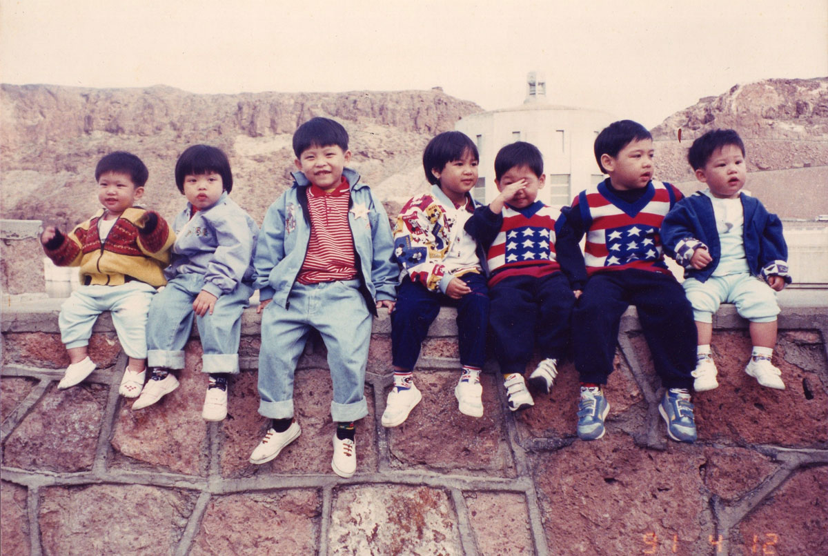 """Jirayut """"New"""" Latthivongskorn as a baby alongside family and friends sitting on a wall."""