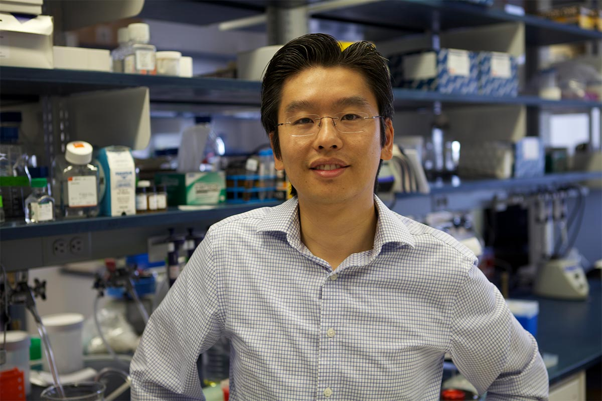 Harris Wang standing in a lab in front of scientific equipment.