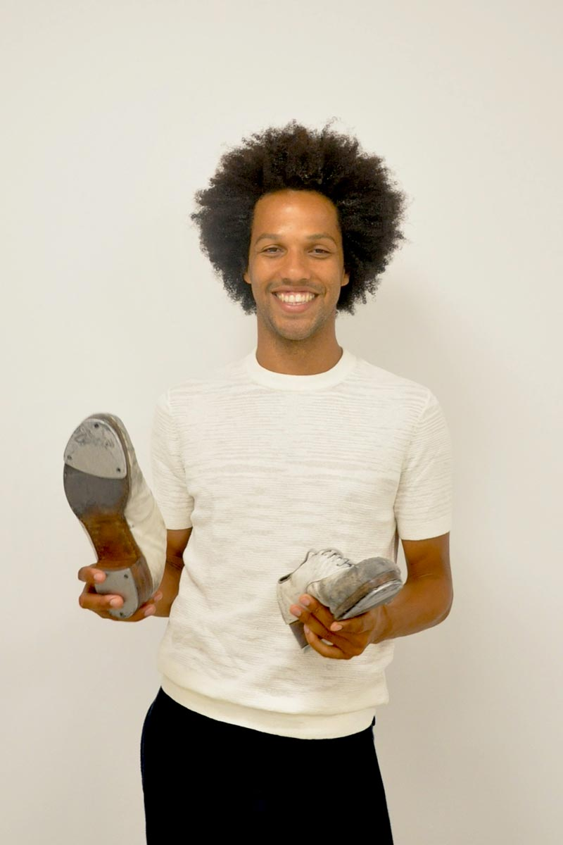 Photo of Leonardo Sandoval holding his tap shoes.