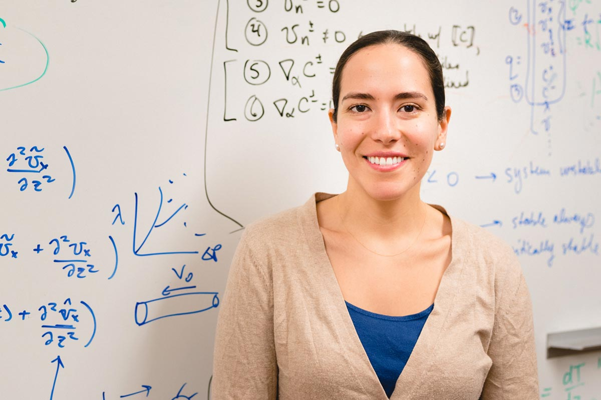 Markita Landry standing in front of a whiteboard with scientific equations.