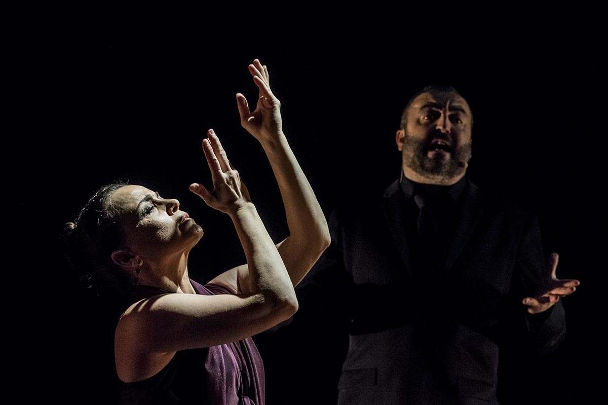 Soledad Barrio, arms raised in air, performs flamenco while a musician sings in the background.